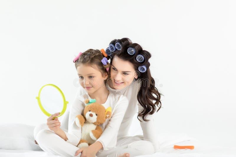 Mãe feliz e filha que abraçam ao guardar o espelho de mão e o urso de peluche imagem de stock