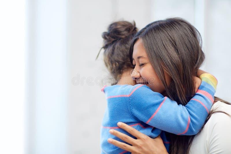 Mãe feliz e filha que abraçam em casa fotografia de stock royalty free