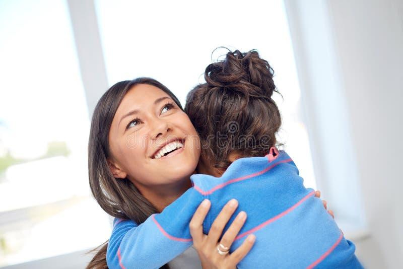 Mãe feliz e filha que abraçam em casa foto de stock royalty free
