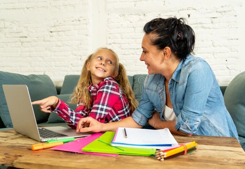 Mãe feliz e filha que fazem trabalhos de casa e que estudam junto fotos de stock