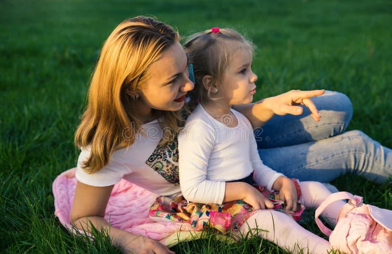 Mãe feliz e filha que jogam no parque que tem o piquenique fotografia de stock royalty free