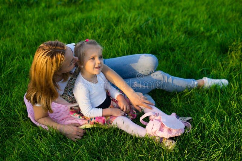 Mãe feliz e filha que jogam no parque que tem o piquenique foto de stock royalty free