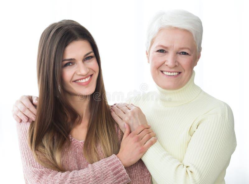 Mãe feliz e filha que levantam e que olham a câmera imagem de stock