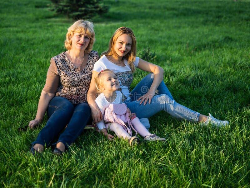 Mãe feliz e filha que sorriem no parque que tem o piquenique fotografia de stock royalty free