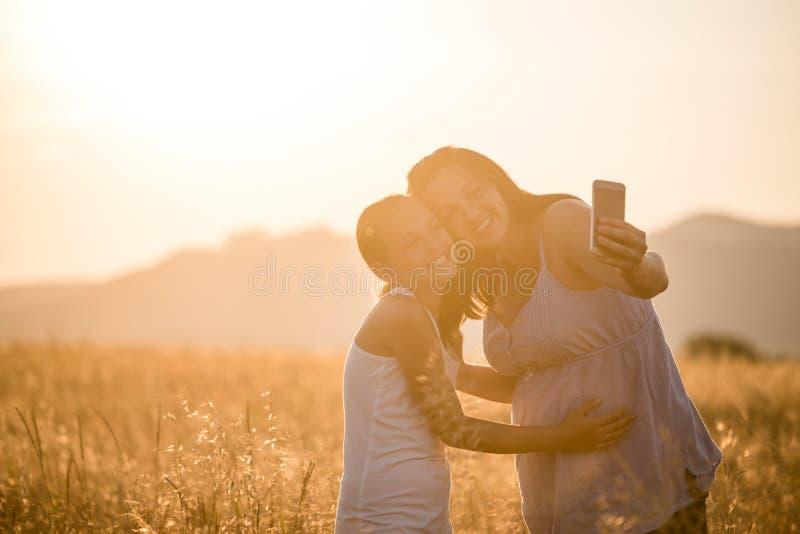 Mãe feliz e filha que tomam o selfie pelo smartphone fora fotografia de stock