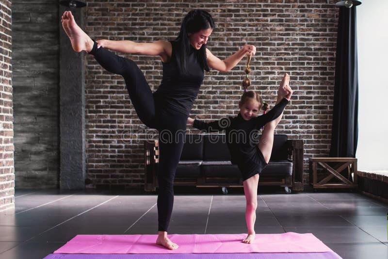 Mãe feliz e filha que vestem o sportswear preto que tem o divertimento ao fazer o pé que estica o exercício que está em um pé em imagem de stock