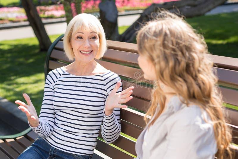 Mãe feliz e filha superiores que sentam-se no banco de parque fotos de stock royalty free