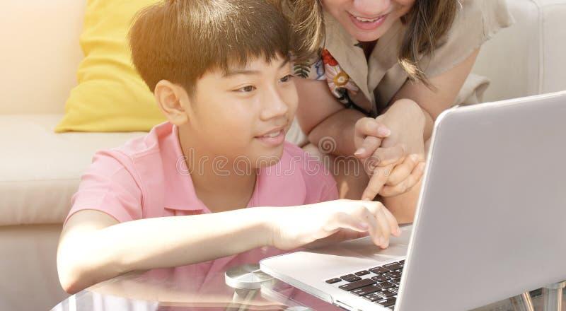 Mãe feliz e filho do pai da família que olham no laptop imagem de stock royalty free