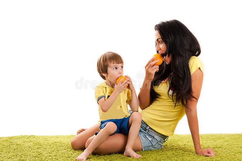 Mãe feliz e filho que comem laranjas imagens de stock