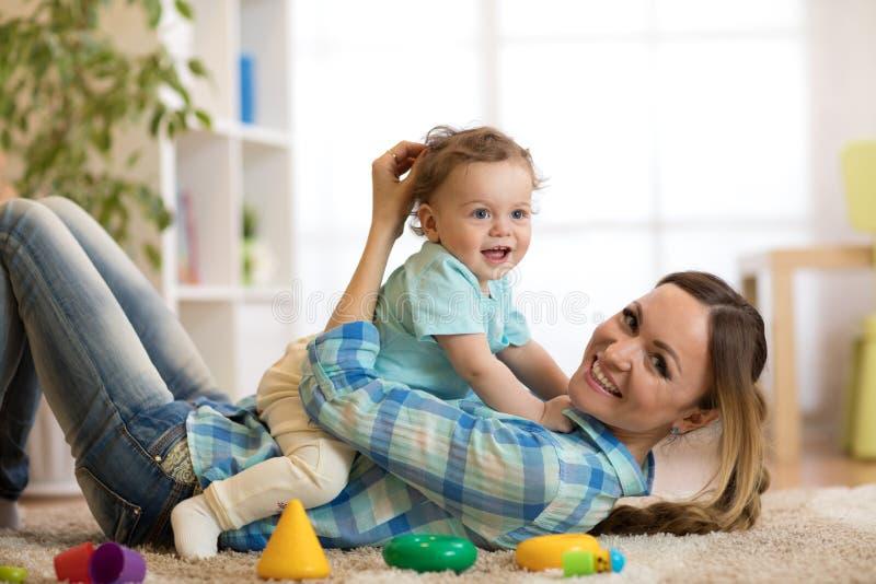 Mãe feliz e filho que encontram-se no assoalho e no jogo internos imagem de stock