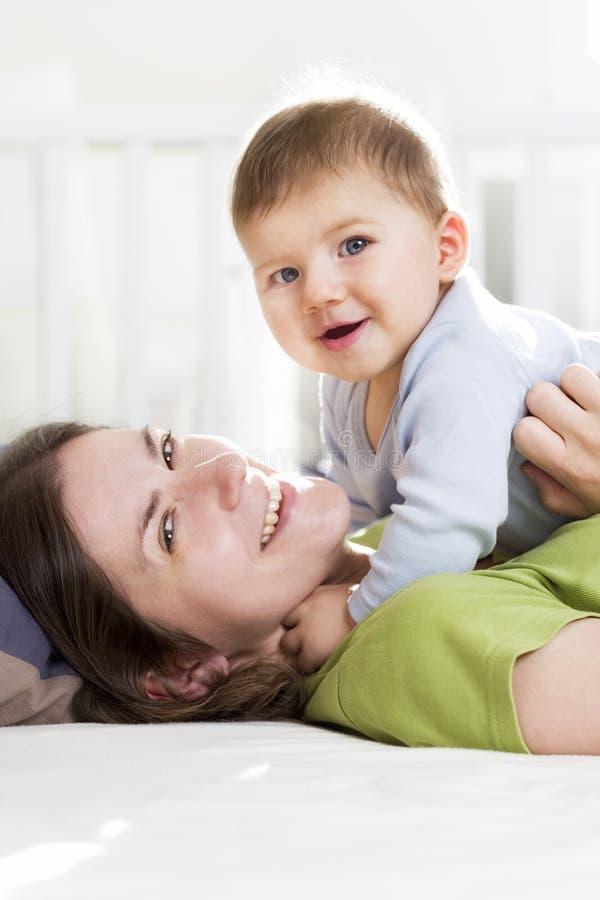 Mãe feliz e filho que jogam e que têm o divertimento na cama. foto de stock royalty free