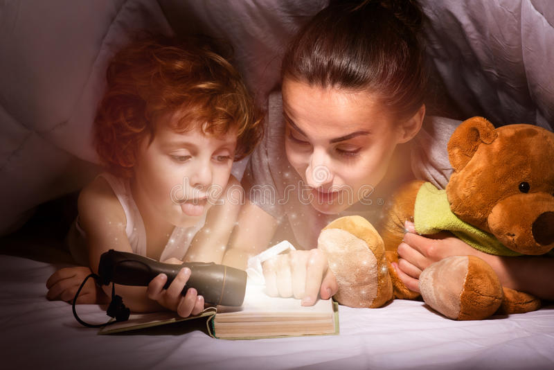 Mãe feliz e filho que leem um livro sob a cobertura fotografia de stock