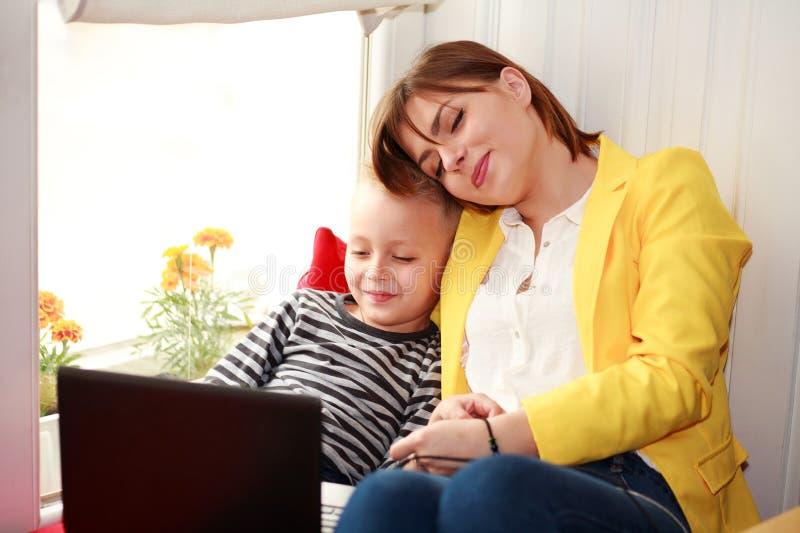 Mãe feliz e filho que olham o portátil em casa fotos de stock royalty free