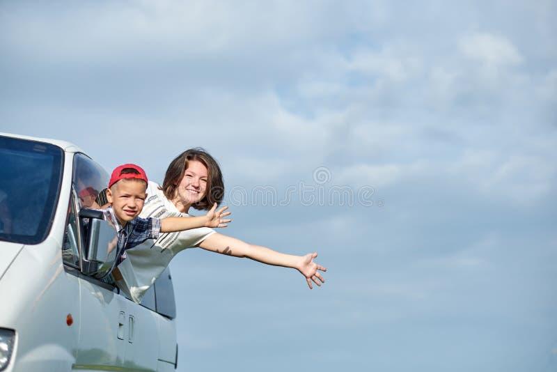 Mãe feliz e filho que olham para fora das janelas e que apreciam a viagem por estrada Fam?lia que viaja pelo carro imagens de stock
