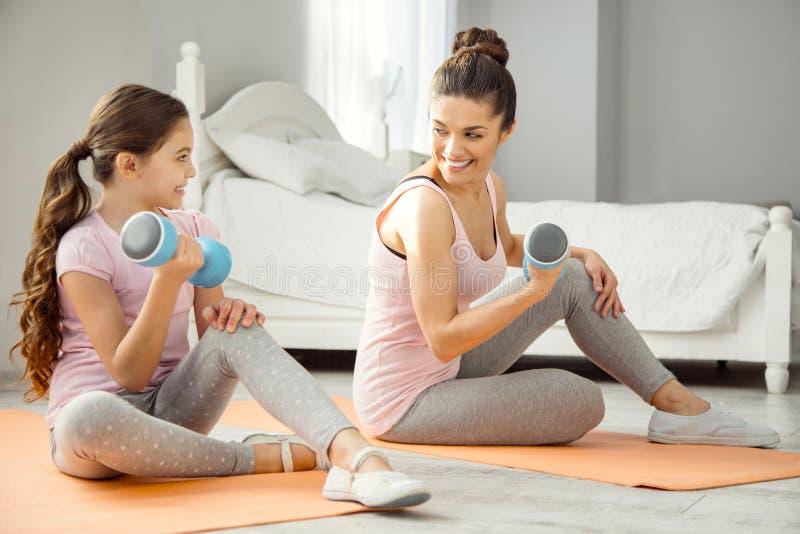 Mãe feliz e menina que fazem exercícios com pesos da mão imagens de stock royalty free