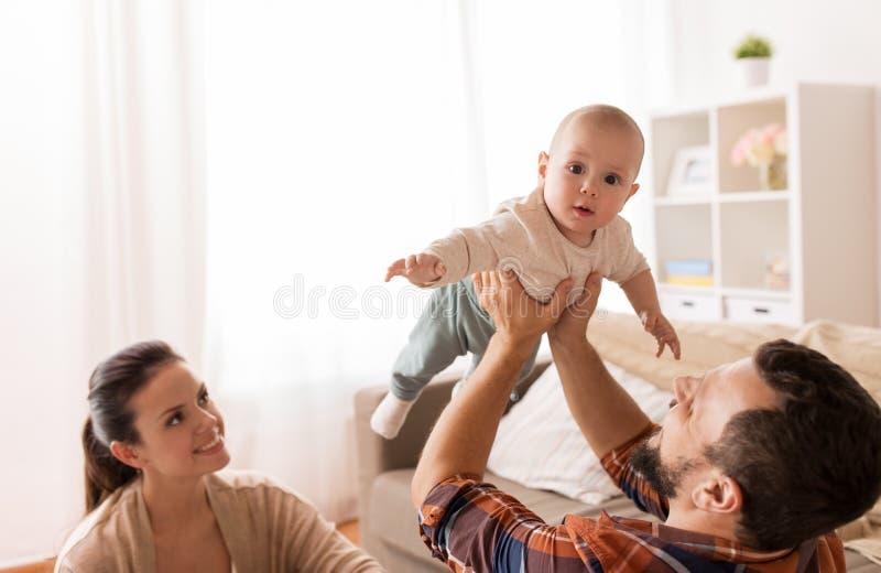 Mãe feliz e pai que jogam com bebê em casa imagem de stock