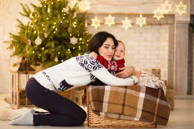 A mãe feliz e seu filho pequeno estão no fundo da árvore de Natal foto de stock