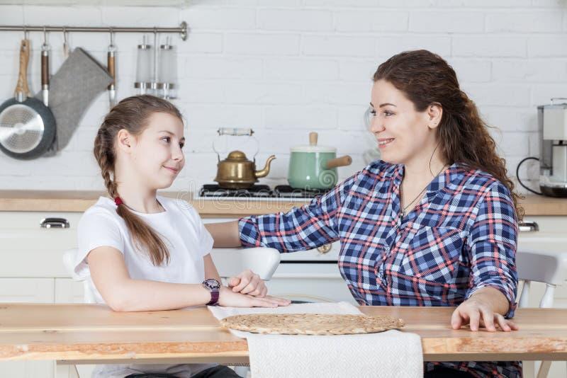 Mãe feliz e sorrindo que fala com sua filha pre adolescente ao sentar-se na tabela na cozinha imagem de stock