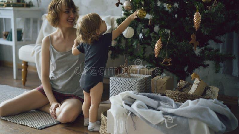 Mãe feliz e sua filha pequena que jogam perto da árvore de Natal em casa fotografia de stock royalty free