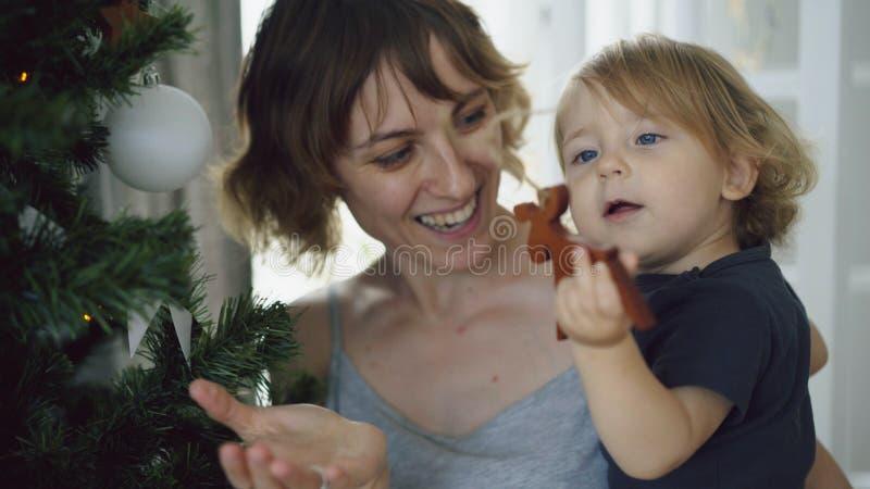Mãe feliz e sua filha pequena que jogam perto da árvore de Natal em casa foto de stock royalty free
