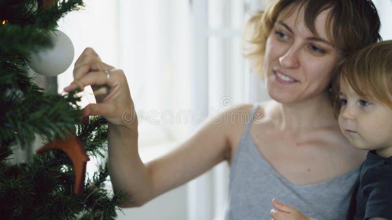 Mãe feliz e sua filha pequena que jogam perto da árvore de Natal em casa foto de stock
