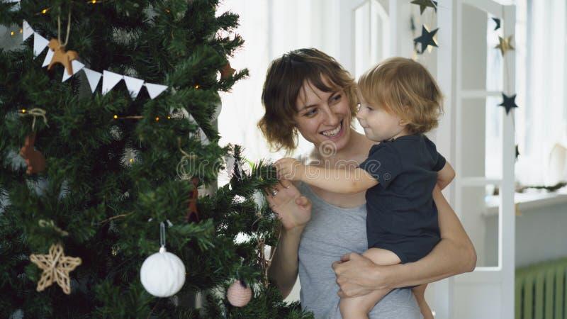 Mãe feliz e sua filha pequena que jogam perto da árvore de Natal em casa imagens de stock royalty free