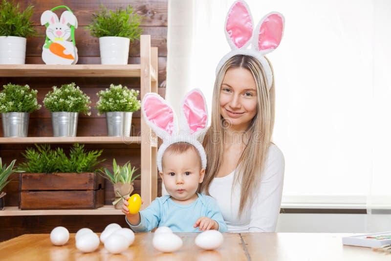 Mãe feliz e suas orelhas vestindo do coelho da criança bonito, preparando-se para a Páscoa fotos de stock royalty free