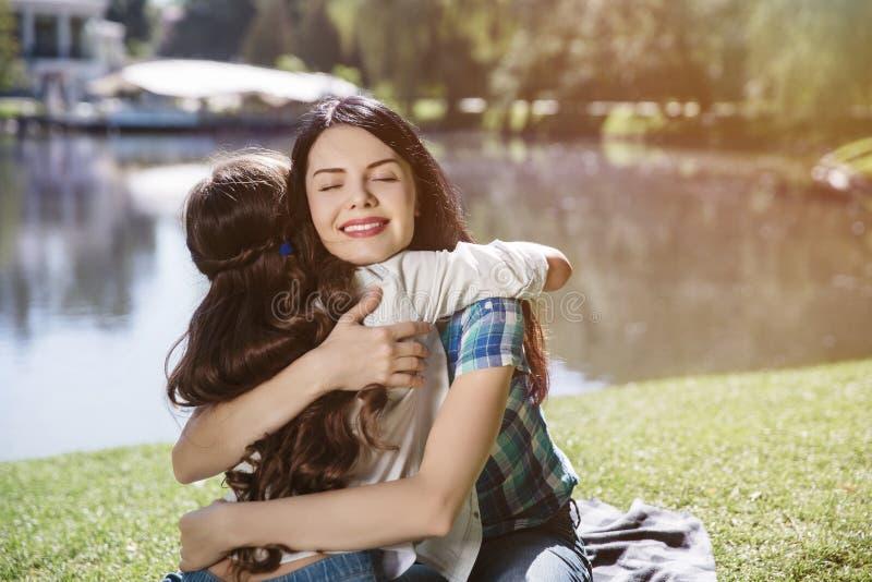 A mãe feliz está sentando-se com sua filha na grama Está abraçando a criança A mulher está mantendo os olhos a fechado e sorrindo imagem de stock