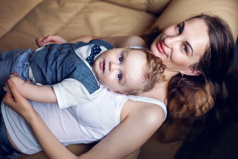 Mãe feliz na camiseta de alças branca que coloca com meu filho em um sofá leve foto de stock royalty free