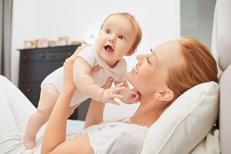 Mãe feliz no jogo do bebê na cama imagens de stock