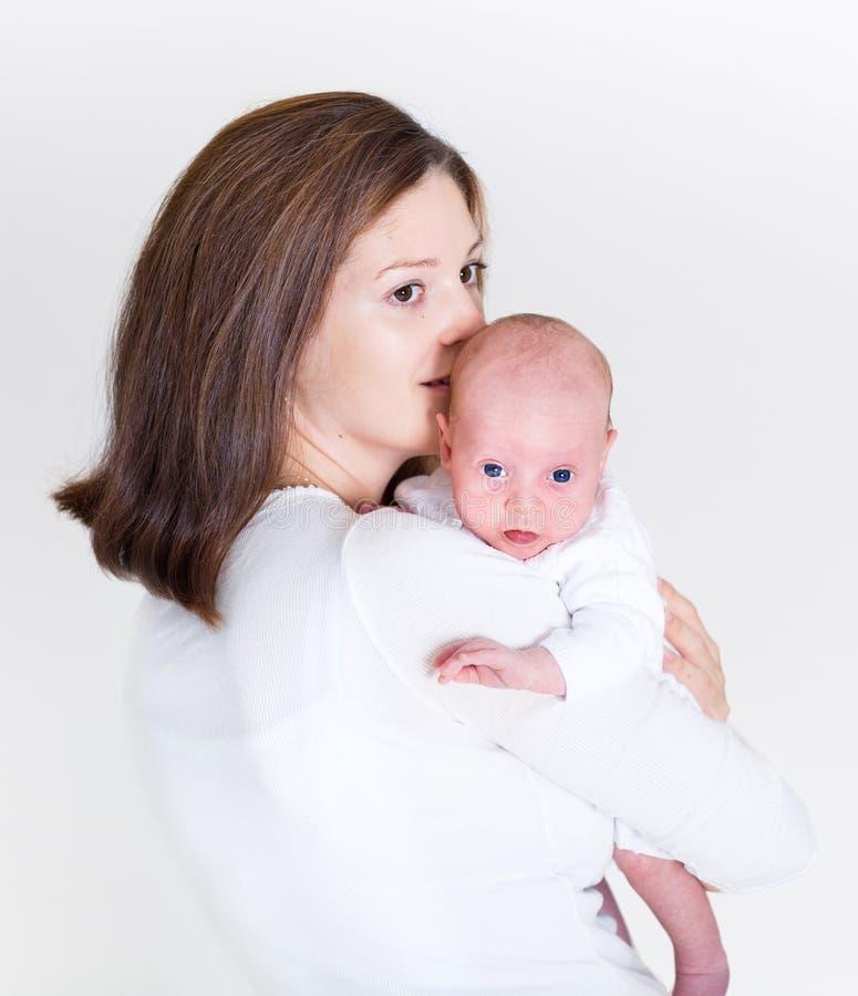 Mãe feliz nova que beija seu bebê recém-nascido imagens de stock