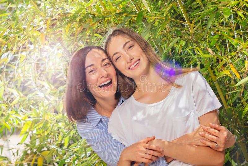 Mãe feliz que abraça a filha adulta da parte traseira imagens de stock