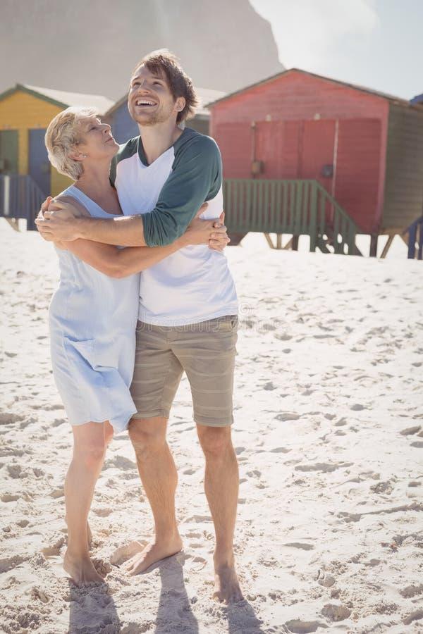 Mãe feliz que abraça seu filho ao estar na praia fotos de stock royalty free