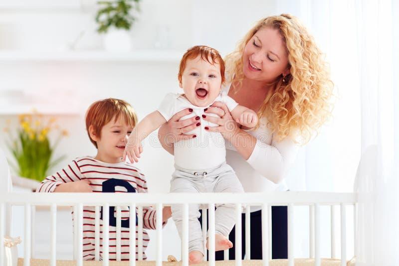 Mãe feliz que aprecia a maternidade, jogando com crianças em casa fotografia de stock royalty free