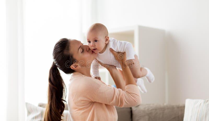 Mãe feliz que beija o bebê pequeno em casa imagem de stock