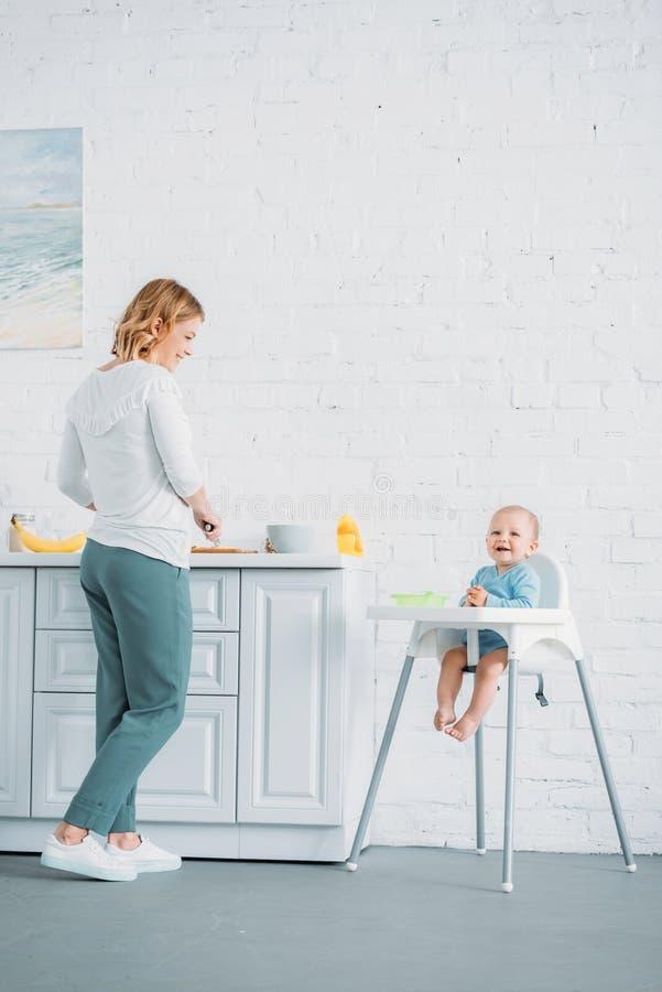 mãe feliz que cozinha o jantar para sua criança foto de stock royalty free