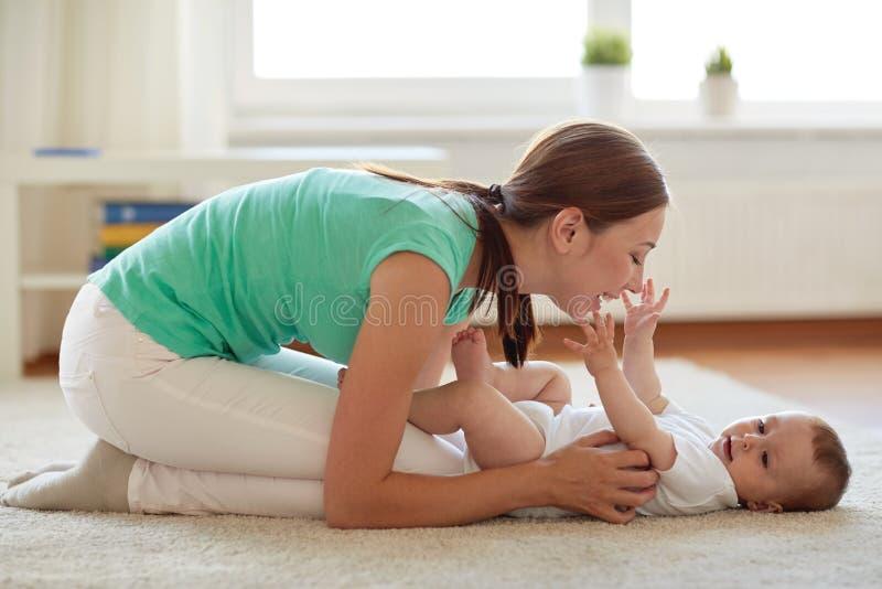 Mãe feliz que joga com bebê em casa foto de stock