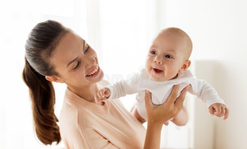 Mãe feliz que joga com bebê pequeno em casa imagem de stock royalty free
