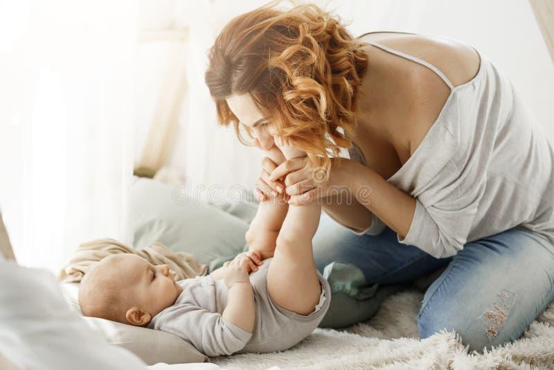 Mãe feliz que joga com os pés pequenos de beijo do bebê recém-nascido que passam os melhores momentos de maternidade no quarto ac fotografia de stock royalty free