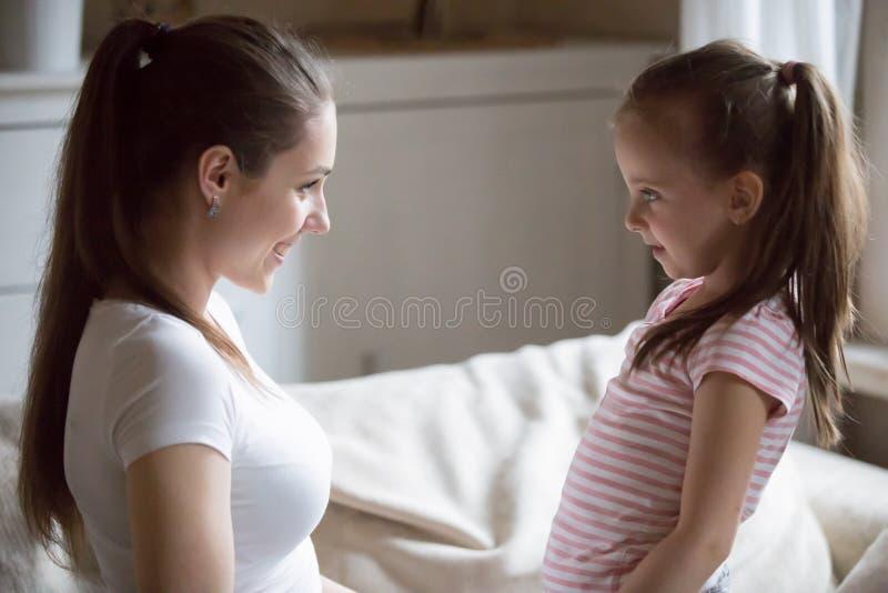 Mãe feliz que olha a filha de sorriso que guarda suas mãos fotografia de stock