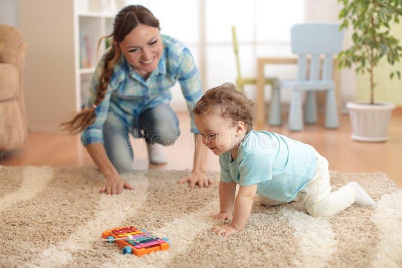 Mãe feliz que olha seu filho de rastejamento do bebê foto de stock royalty free