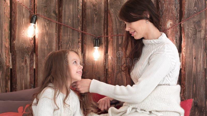 Mãe feliz que penteia seu cabelo do ` s da filha foto de stock royalty free