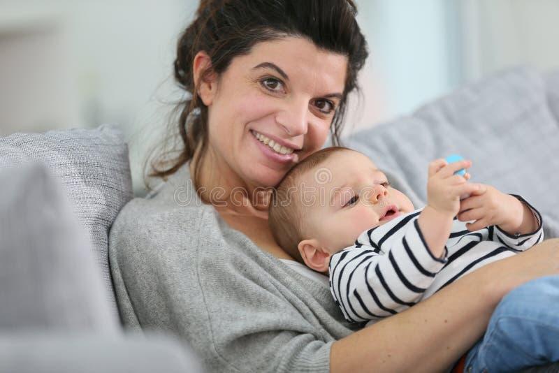 Mãe feliz que relaxa com seu bebê em um sofá foto de stock