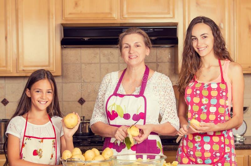 Mãe feliz, sorrindo e suas filhas que cozinham o jantar foto de stock royalty free
