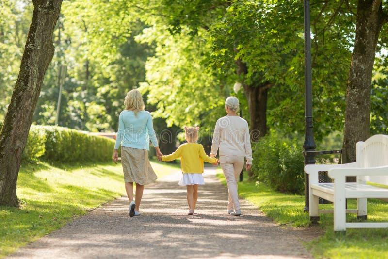Mãe, filha e avó andando no parque fotografia de stock