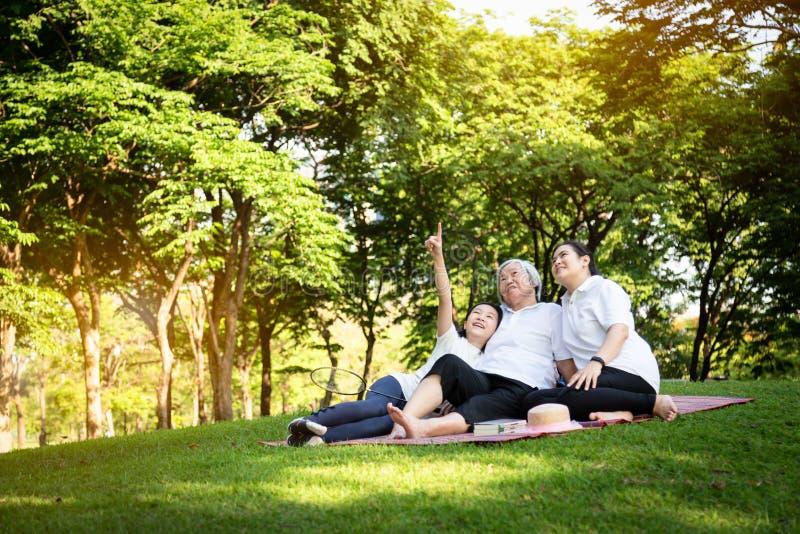 Mãe, filha que olha algo interessante com avó superior em uma esteira no parque exterior, mulher idosa asiática de sorriso feliz imagens de stock
