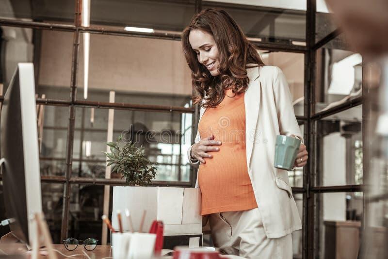 Mãe futura alegre que mantém sua barriga grávida ao encher a caixa imagens de stock