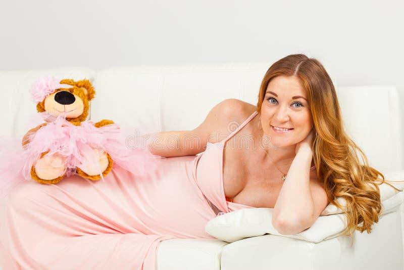 A mãe futura encontra-se em um sofá branco foto de stock royalty free