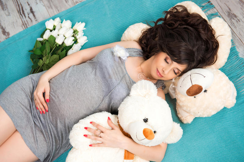 Mãe grávida bonita com ursos de peluche motherhood imagem de stock royalty free