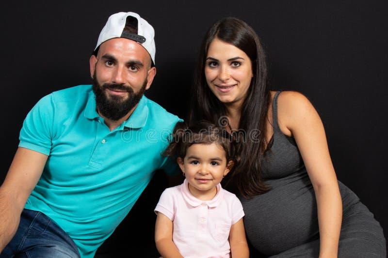 A mãe grávida com sua família senta-se no fundo do preto do assoalho fotografia de stock